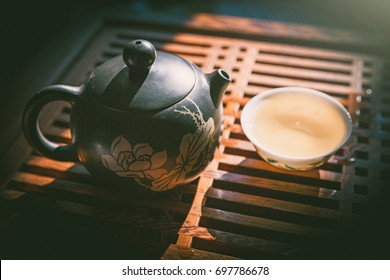 Chinese tea ceremony. Teapot and a cup of green puer tea on wooden table. Asian traditional culture ceremony.
