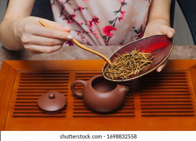 Chinese tea ceremony. Woman pouring tea into a teapot using a wooden stick. Clay teapot stand on wooden tray.