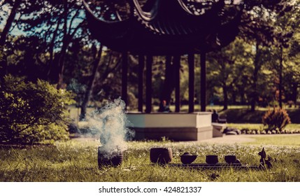 Chinese tea ritual in summer park with traditional chinese arbour on background.