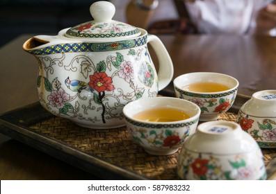 Chinese tea set, closeup vintage teapot and cup on bamboo mat