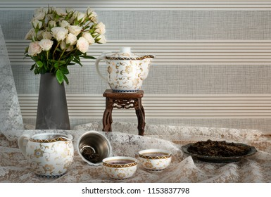 Chinese tea set of Pu'er tea in Chinese pot, small jar, two cups of tea and filter with dry fermented tea leaves in plate on lace table cover with vase of white rose