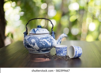 Chinese teapot and tea cups with dried tea leaf on dark brown table in green garden / Selective focus