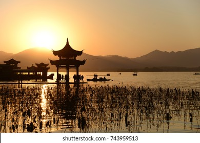 Chinese temple in west lake with sunset, China
