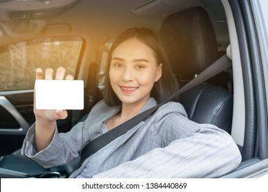 Chinese Thai Asian Woman showing her blank driving license  while in the car