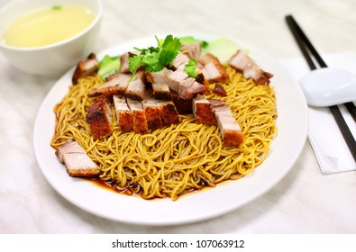 Chinese Tossed Egg Noodle with Roasted Pork on Top isolated on white