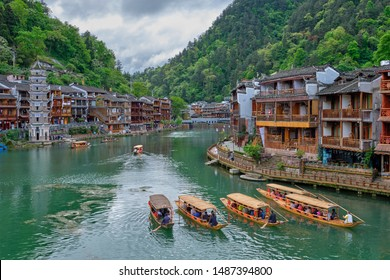 Chinese tourist attraction destination - Feng Huang Ancient Town (Phoenix Ancient Town) on Tuo Jiang River with Wanming Pagoda tower and tourist boats. Hunan Province, China