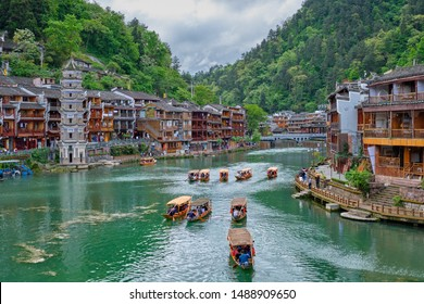 Chinese tourist attraction destination - Feng Huang Ancient Town (Phoenix Ancient Town) on Tuo Jiang River with Wanming Pagoda tower and tourist boat. Hunan Province, China