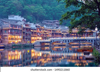 Chinese tourist attraction destination - Feng Huang Ancient Town (Phoenix Ancient Town) on Tuo Jiang River with bridge illuminated at night. Hunan Province, China