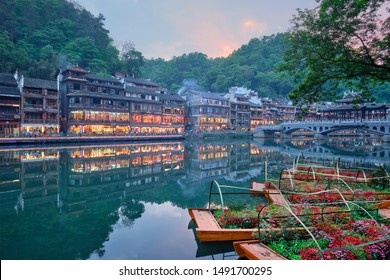Chinese tourist attraction destination - Feng Huang Ancient Town (Phoenix Ancient Town) on Tuo Jiang River with flower beds on boats illuminated at night. Hunan Province, China