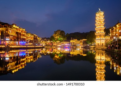 Chinese tourist attraction destination - Feng Huang Ancient Town (Phoenix Ancient Town) on Tuo Jiang River with Wanming Pagoda illuminated at night. Hunan Province, China