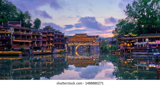 Chinese tourist attraction destination - panorama of Feng Huang Ancient Town (Phoenix Ancient Town) on Tuo Jiang River illuminated at night. Hunan Province, China