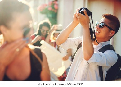 Chinese tourist is photographing architecture in old town. He is in a group of multiracial people.Exploring, searching, traveling. Friendship goals.