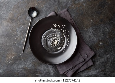 Chinese tradition food. Black sesame sweet soup in black plate. black plate background. Oriental dessert. Top view. Trandy food.