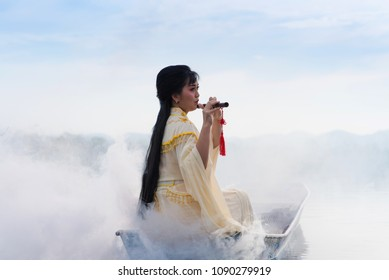 Chinese traditional traditional dress playing Traditional Chinese Flute on an ancient ship