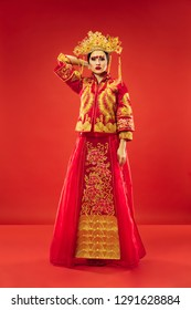 Chinese traditional graceful woman at studio over red background. Beautiful girl wearing national costume. Chinese New Year, elegance, grace, performer, performance, dance, actress, lunar concept