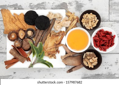Chinese traditional herbal medicine selection with honey over distressed wooden background.