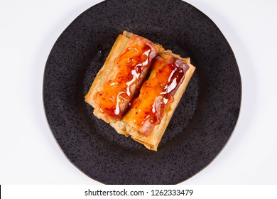 Chinese Traditional Spring rolls with sweet and sour sauce on a black plate
