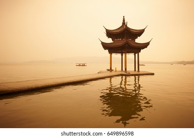 Chinese traditional wooden pavilion on the coast of West Lake, public park in Hangzhou city, China