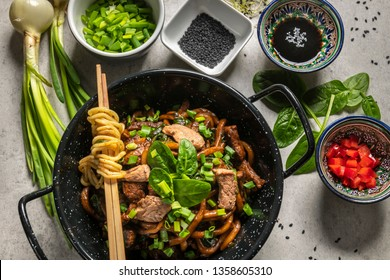 Chinese udon noodles with beef and vegatables fried in a pan on the gray table.  Top view
