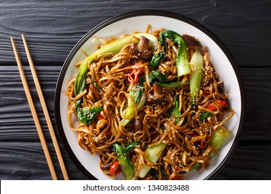 Chinese udon noodles with bok choy, shiitake mushrooms  and pepper close-up on a plate on the table. horizontal top view from above