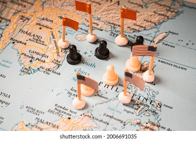 Chinese and U.S. flags with chess pieces symbolizing the conflict and control of the South China Sea.