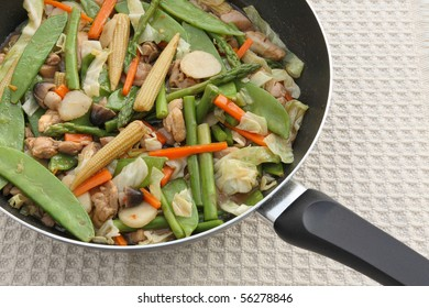 chinese vegetable and chicken stir-fry in skillet close-up