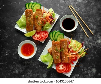 Chinese vegetable spring rolls garnished with fresh salad, lime wedges, sweet chilli sauce and soy sauce