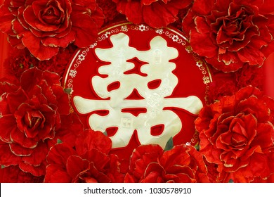 Chinese wedding symbol paper cut and red flowers decorated on the wall. Chinese Wedding with Double Happiness Text Calligraphy Illustration on paper cut design.