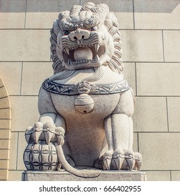 A chinese white lion stone statue with stone brick wall background.