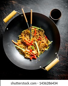 Chinese wok. Delicious cellophane noodles with salmon. On dark rustic background