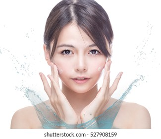 Chinese woman applying cream to face with water splash. skincare concept
