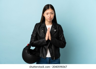 Chinese woman holding a motorcycle helmet over isolated blue background pleading