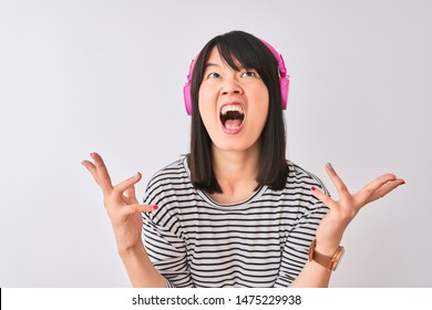 Chinese woman listening to music using pink headphones over isolated white background crazy and mad shouting and yelling with aggressive expression and arms raised. Frustration concept.