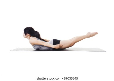 Chinese woman on a yoga mat doing the locust pose.