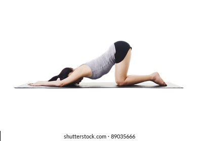 Chinese woman on a yoga mat doing the extended puppy pose.
