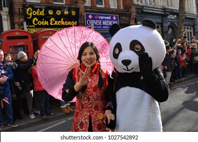 Chinese woman and person in panda costume in China Town, London, at the Chinese New Years Celebrations, February 2018.