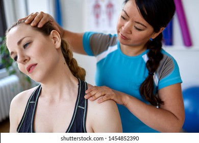 Chinese woman physiotherapy professional giving a treatment to an attractive blond client in a bright medical office
