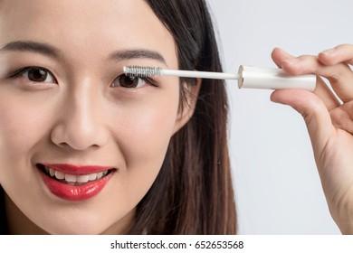 Chinese woman putting mascara on eyelashes on gray background