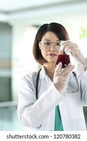 Chinese woman scientist or Doctor looking at a liquid solution.