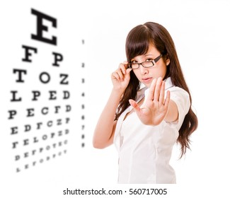 Chinese woman showing no with hand next to eyesight test chart