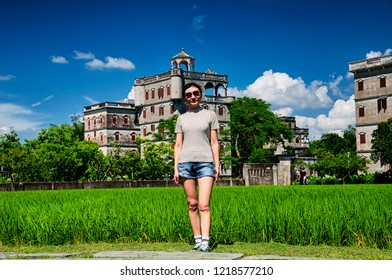 A chinese woman standing at the edge of rice paddy at the historic buildings of Kaiping Diaolou in Zili village in Kaiping China in Guangdong province on a sunny blue sky day.