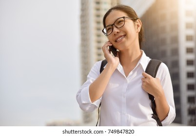 Chinese Woman talking with someone on her mobile phone on skyscraper building background in the city. Copy space.