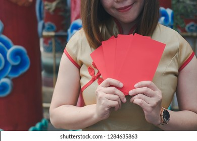 Chinese woman in traditional clothing holding red envelope or Ang-pao feeling happiness from a Chinese new year gift. Happy chinese new year concept