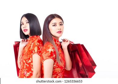 Chinese woman wear qipao and holding shopping bag in hand, isolated on white background
