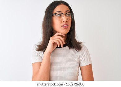 Chinese woman wearing casual t-shirt and glasses standing over isolated white background with hand on chin thinking about question, pensive expression. Smiling with thoughtful face. Doubt concept.