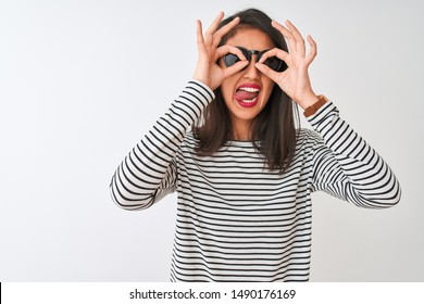 Chinese woman wearing striped t-shirt and sunglasses standing over isolated white background doing ok gesture like binoculars sticking tongue out, eyes looking through fingers. Crazy expression.
