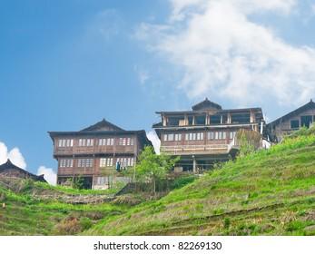 Chinese wooden buildings beside rice terrace, at Longji, Guilin, Guangxi Province, China