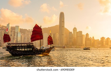 Chinese wooden red sails ship in Hong Kong Victoria harbor at sunset time