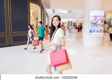 chinese young girl, wearing a stylish white dress, walking in the mall