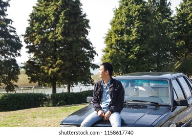 A Chinese Young Man's side face Sitting on the Car